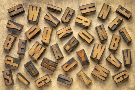 random letters overhead background - vintage letterpress wood type of different fonts  (inverted image)  against brown handmade bark paper