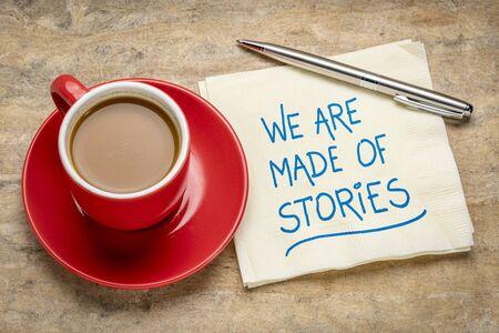 Estamos hechos de historias: escritura a mano en una servilleta con una taza de café, concepto de narración Foto de archivo