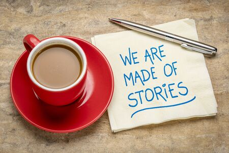 We are made of stories - handwriting on a napkin with a cup of coffee, storytelling concept Banco de Imagens