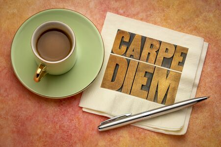 Carpe Diem  - enjoy life before it is too late, existential cautionary Latin phrase by Horace -  text in vintage letterpress wood type printing blocks on a napkin  with a cup of coffee Stock Photo