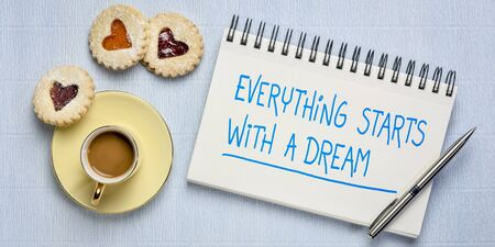 everything starts with a dream inspiration note in sketchbook with a cup of coffee and heart cookies, startup business and success concept
