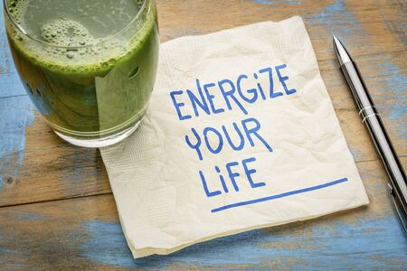 energize your life - inspirational handwriting on a napkin with a glass of green juice, healthy eating and lifestyle concept
