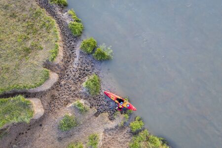 kayaker on a muddy shore of Dismal River in Nebraska - overhead aerial view near Whitetail Campground at Nebraska National Forest