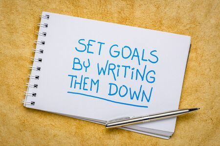 set goals by writing them down reminder - handwriting in a spiral sketchbook, planning, setting and recording goals concept