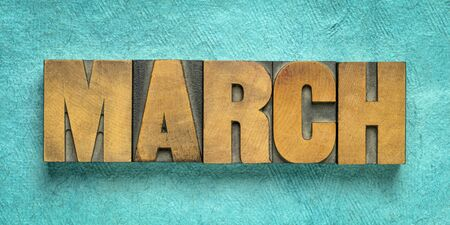 March month banner - word in vintage letterpress wood type against  turquoise  handmade textured paper - calendar concept 写真素材