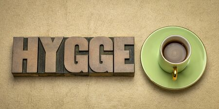 hygge word in vintage letterpress wood type blocks against handmade bark paper with a cup of coffee, Danish cozy lifestyle concept 스톡 콘텐츠