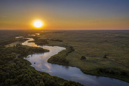 sunrise over Dismal River meandering through Nebraska Sandhills at Nebraska National Forest, aerial view of summer scenery Stock Photo
