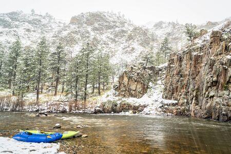 Whitewater kayak gonfiabile e packraft su una riva del fiume di montagna in una forte tempesta di neve primaverile - Poudre River nel nord del Colorado