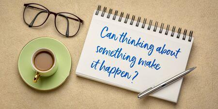 ¿Pensar en algo puede hacer que suceda? Escritura a mano en un cuaderno de bocetos con taza de café plana. Concepto de ley de atracción.
