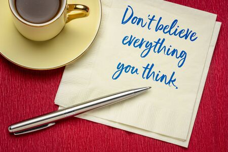 Do not believe everything you think - handwriting on a napkin with a cup of coffee, warning concept