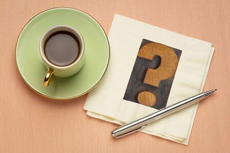 question mark in vintage letterpress wood type on a napkin with coffee, question, doubt or uncertainty concept Standard-Bild