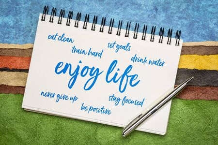enjoy life - healthy, happy and positive lifestyle word cloud on a sketchbook against colorful paper abstract landscape