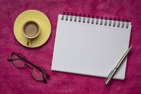 blank spiral art sketchbook with a pen, reading glasses and a cup of coffee against textured bark paper, workspace flat lay
