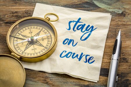 Stay on course reminder - motivational handwriting on a napkin with an antique brass compass, navigation, determination and setting goals concept Banque d'images