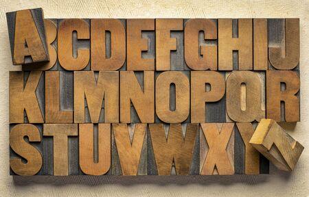 Alphabet in Vintage-Buchdruck-Holzdruckstöcken gegen handgeschöpftes Rindenpapier Standard-Bild