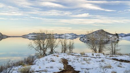Partially frozen calm lake at foothills of Rocky Mountains - Horsetooth Reservoir, a part of Big Thompson Project and a popular recreation destination near Fort Collins in northern Colorado, winter scenery.