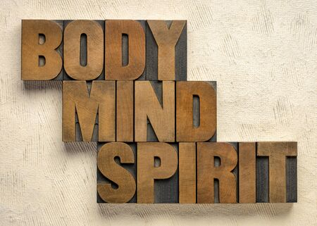 body, mind and spirit - words in vintage wood letterpress printing blocks against textured paper, holistic wellness and lifestyle concept Foto de archivo