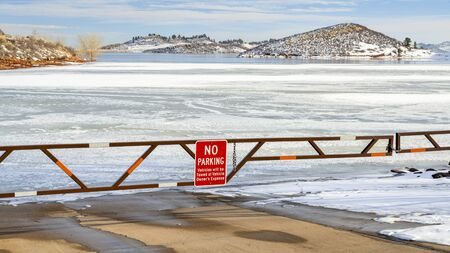 Boat ramp closed for winter on a frozen lake at foothills of Rocky Mountains - Horsetooth Reservoir, a popular recreation destination near Fort Collins in northern Colorado. 写真素材
