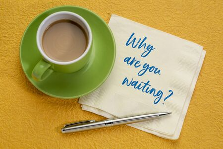 Why are you waiting? Hadwiting on a napkin with a cup of coffee. Encouragement and motivation concept. Stockfoto