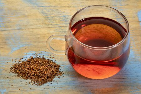 rooibos red tea - a glass cup of a hot drink and loose leaves, tea made from the South African red bush, naturally caffeine free