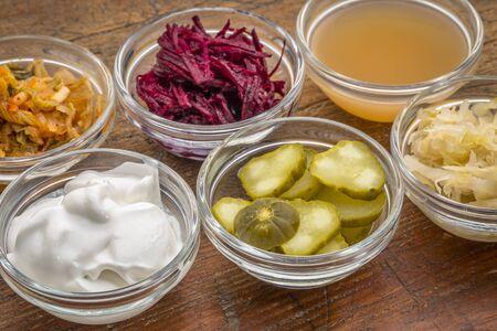 a sampler of fermented, prebiotics, food great for gut health - glass bowls against wood: kimchi, red beets, apple cider vinegar, coconut milk yogurt, cucumber pickles, sauerkraut
