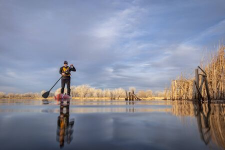 senior male paddler in a wetsuit is paddling a stand up paddleboard on a lake in Colorado, winter or early spring scenery, low angle action camera view, recreation, fitness and training concept