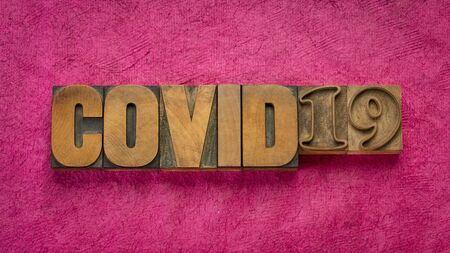 covid-19 word abstract in vintage letterpress wood type against handmade bark paper, , coronavirus outbreak and pandemic concept 写真素材