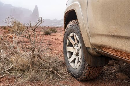 4x4 SUV car or truck driving on a trail in winter conditions - Fisher Towers in Moab area, Utah, off-road driving, recreation and travel concept