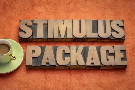 stimulus package word abstract in vintage letterpress wood type with coffee against textured handmade paper