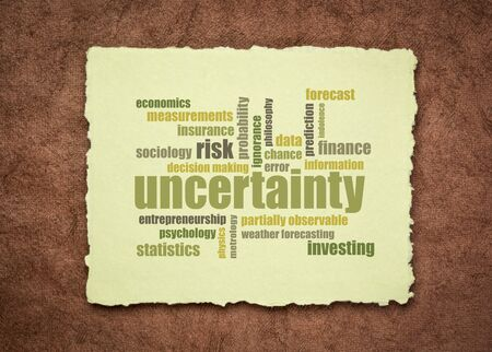 uncertainty and risk word cloud on a sheet of a soft handmade rag paper, business decision making and forecast concept 版權商用圖片