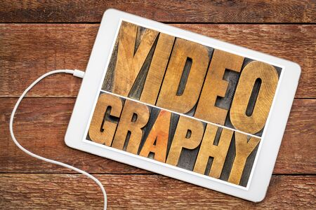 videography word abstract in vintage letterpress wood type on a digital tablet, media, entertainment and communication concept