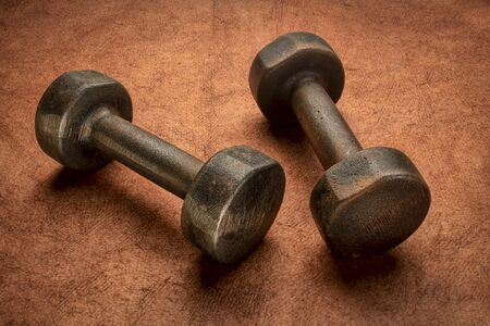 old rusty dumbbells on textured brown handmade bark paper, fitness and exercise concept