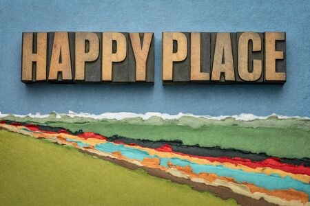 happy place - word abstract in vintage letterpress wood type against abstract paper river landscape, joy and happiness concept - a memory, situation, or activity that makes you feel happy