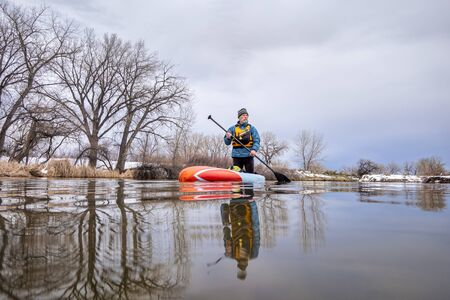 solo lake paddling as social distancing recreation during coronavirus pandemic, a senior male paddler on stand up paddleboard in early spring in Colorado