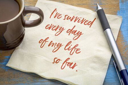 I have survived every day of my life so far - positive affirmation, inspirational handwriting on a napkin with a cup of coffee. Personal development and motivation concept. Stock Photo
