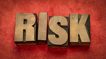 risk word abstract in vintage letterpress wood type against red textured paper, business, danger and uncertainty concept
