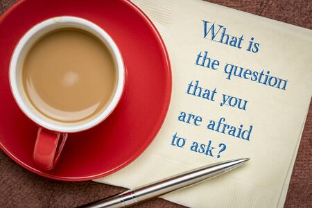 What is the question that you are afraid to ask? Handwriting on a napkin with a cup of coffee. Difficult question and personal development concept.