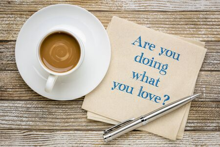 Are you doing what you love? Inspirational question on a napkin with a cup of coffee. Career and personal development concept. Stock Photo