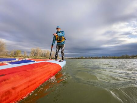 Low angle view from action camera of a senior male paddler on a long racing stand up paddleboard on a lake in Colorado.  Recreation, training and fitness concept.