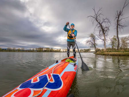 Fort Collins, CO, USA - May 10, 2020:  Low angle view from action camera of a senior male paddler on a long racing stand up paddleboard - Mistral Stealth.   Recreation, training and fitness concept.