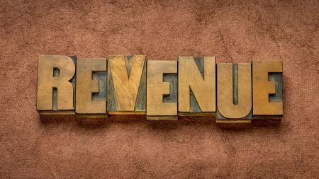 revenue  word abstract in vintage letterpress wood type against handmade paper, business, income and accounting concept