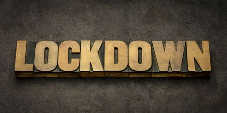 lockdown word abstract in vintage letterpress wood type against handmade paper, prison protocol or emergency measures during coronavirus covid-19 pandemic
