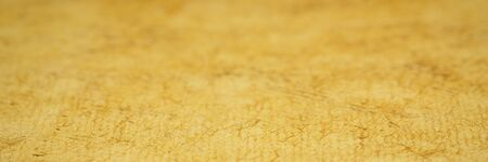 background and texture of yellow huun handmade paper with a selective focus, panoramic web banner