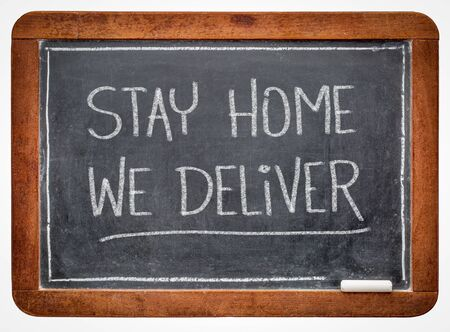 stay home we deliver - white chalk handwriting on a slate blackboard, home delivery service during coronavirus covid-19 pandemic and social distancing