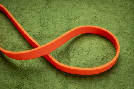 resistance exercise band for fitness and rehabilitation against green background Stock Photo