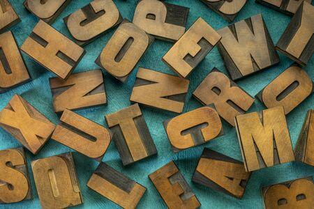 random letters overhead background - vintage letterpress wood type (inverted image)  against turquoise  handmade bark paper Stock Photo
