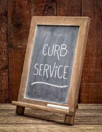 curb service sign - white chalk handwriting on a blackboard, service extended (as by a restaurant) to persons sitting in parked automobiles, social distancing measure during coronavirus pandemic