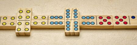 row of wooden domino pieces with colorful pips (dots), panoramic web banner Stock Photo