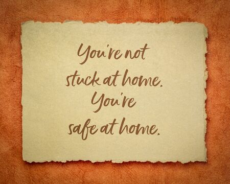 you are not stuck at home, you are safe at home - inspirational note on a handmade rag paper, reminder for self isolation or quarantine during coronavirus pandemic