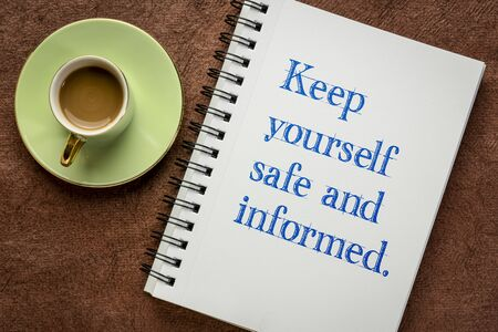keep yourself safe and informed - motivational handwriting in a spiral notebook with a cup of coffee, reminder for coronavirus pandemic crisis